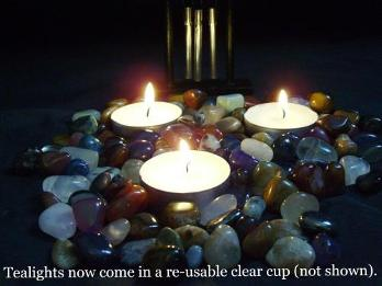 Photograph of 3 tea light candles on tumblestones with small windchime in background.